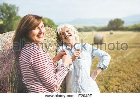 Deux amis de sexe féminin avec de la paille de l'herbe, Toscane, Italie Banque D'Images