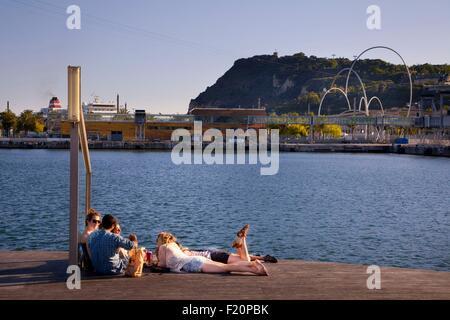 Espagne, Catalogne, Barcelone, le Vieux Port, Vieux Port, Port Vell, Rambla de Mar, pont sur le chat et les jeunes et le bronzage Montjouic Hill, avec les vagues (Les Onades) sculpture d'Alfaro dans l'arrière-plan