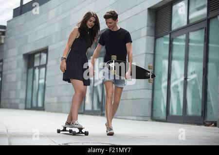 Jeune couple dans l'amour d'adolescents élégant ride longboards Banque D'Images