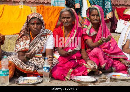 Les pèlerins sont paumes pendant qu'ils attendent de recevoir prasad (la nourriture comme une offrande religieuse) Banque D'Images