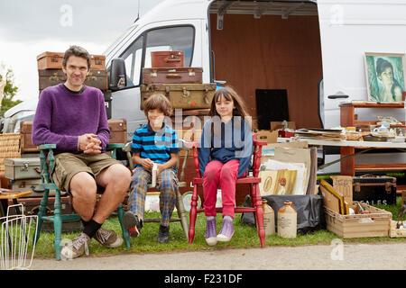 L'homme, garçon et fille avec des troncs et des paniers et des meubles à marché aux puces. Banque D'Images
