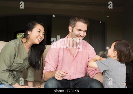 En souriant l'homme et la femme assis côte à côte sur un canapé, jouant avec leur jeune fils. Banque D'Images