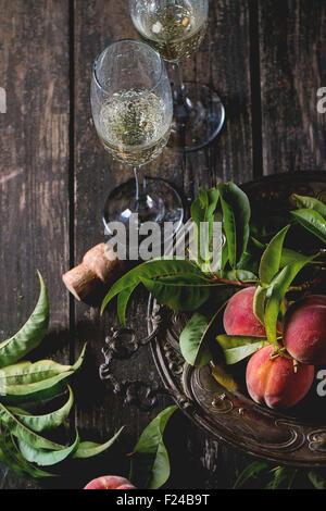Les pêches sur la branche avec des feuilles en vintage et deux verre de champagne avec du liège plus vieille table Banque D'Images