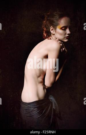 Portrait dramatique d'une jeune fille parmi l'obscurité. Effet texture Grunge Banque D'Images