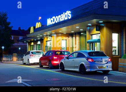 La file de voitures chez McDonald's restaurant drive-in, de nuit, en Angleterre, Royaume-Uni Banque D'Images