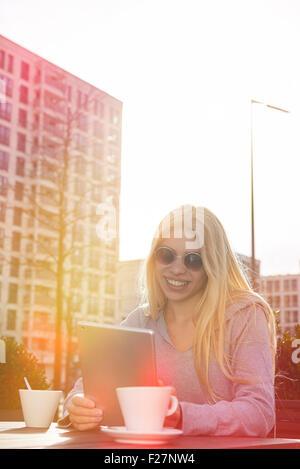 Teenage girl using a digital tablet at sidewalk cafe, Munich, Bavière, Allemagne