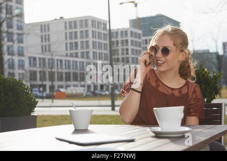 Young Woman talking on a mobile phone at sidewalk cafe, Munich, Bavière, Allemagne