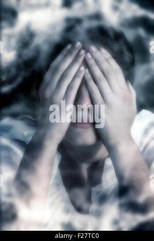 Une femme en détresse, se cacher derrière ses mains Banque D'Images
