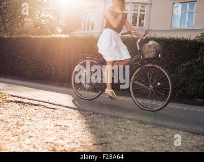 Cropped shot of woman riding bicycle le long de la rue. Cyclisme féminin sur route avec Sun flare.