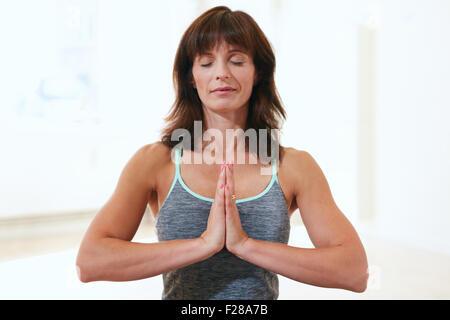 Portrait d'une belle mature woman sitting in Anjali Mudra yoga pose dans la salle de sport à méditer. Professeur Banque D'Images