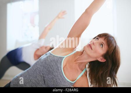 Portrait of young woman at gym. Femme de remise en forme Triangle faisant yoga pose, Trikonasana. Banque D'Images