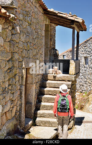 Portugal: Femme à la recherche de chien à l'escalier d'une maison en pierre dans le village historique de Monsanto Banque D'Images
