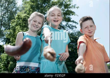Trois amis de la préparation de saucisses sur feu de camp, Bavière, Allemagne Banque D'Images