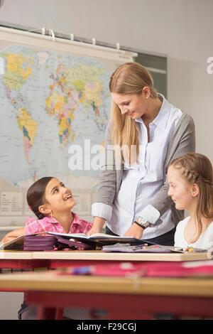 Institutrice aidant les élèves en classe, Munich, Bavière, Allemagne Banque D'Images