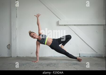 Mid adult woman practicing planche latérale de poser dans un studio de yoga, Munich, Bavière, Allemagne Banque D'Images
