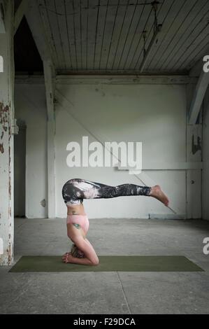 Mid adult woman practicing wavecrest poser dans un studio de yoga, Munich, Bavière, Allemagne Banque D'Images