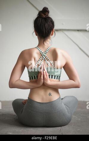 Vue arrière d'un mid adult woman faire pashchima namaskarasana position dans un studio de yoga, Munich, Bavière, Banque D'Images