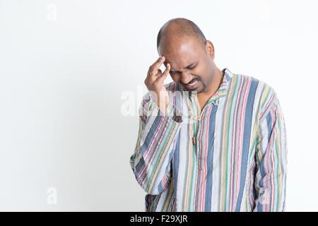 Portrait of Indian man avoir mal de tête, le front, les frotter à la main debout sur fond gris. Banque D'Images