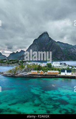 Olstind montage au-dessus des cabines jaunes et jaunes eaux de Sakrisoy village de pêcheurs sur les îles Lofoten en Norvège