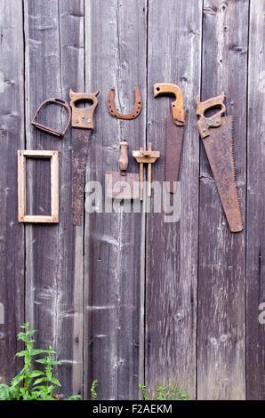 Outils d'artisanat antique et horseshoe pendaison le vieux mur de la grange en bois Banque D'Images