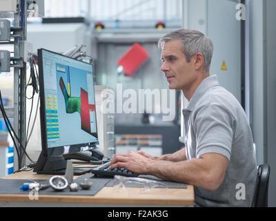 Tour CNC ingénieur regardant des progrès à l'écran dans l'usine d'orthopédie Banque D'Images