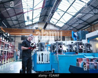 Engineer inspecting pièces sur tour automatique à l'usine d'ingénierie