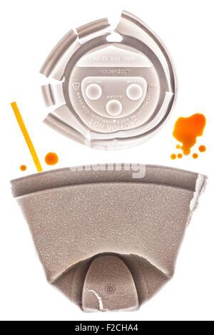 Tasse à café en styromousse aplaties à l'aide ci-dessus et bâtonnet jaune sur la table lumineuse avec des gouttes Banque D'Images