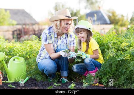 Mère et fille la plantation des semis de fraises en été