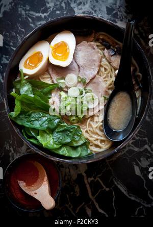 Vue de dessus de ramen avec avec des œufs, des épinards, de porc et de ventre sur table de marbre avec cuillère Banque D'Images