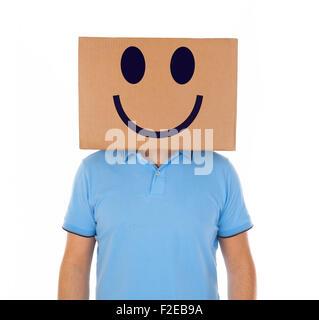Jeune homme debout avec une boîte en carton sur la tête avec des smiley sur fond blanc. Banque D'Images