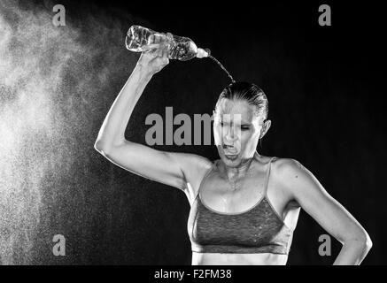 Femme athlétique fatigués verser de l'eau sur la tête Banque D'Images