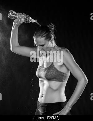 Fit Woman Pouring Water Over Head après entraînement Banque D'Images