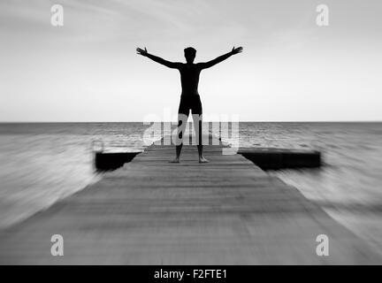 Silhouette d'un homme pacifique sur la jetée de la mer Banque D'Images
