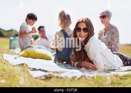 Portrait smiling woman laying on blanket in champ ensoleillé avec la famille Banque D'Images