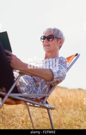 Senior woman reading book in sunny field Banque D'Images