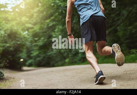 Vue arrière sans tête tourné d'un jeune homme athlétique en marche dans le parc tôt le matin. Banque D'Images