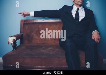 Businessman sitting on sofa and pointing Banque D'Images