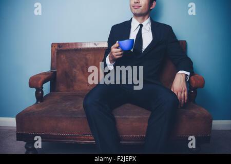 Businessman sur canapé avec une tasse de café Banque D'Images