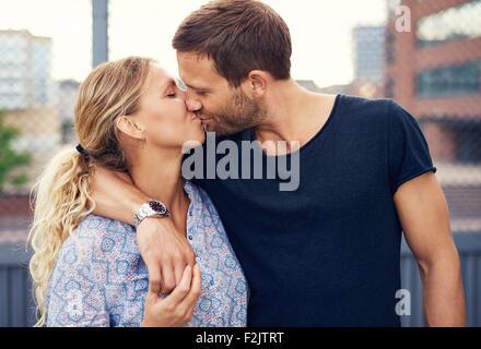 Amorous attractive young couple profitez d'un baiser romantique tels qu'ils sont dans les bras l'extérieur dans Banque D'Images
