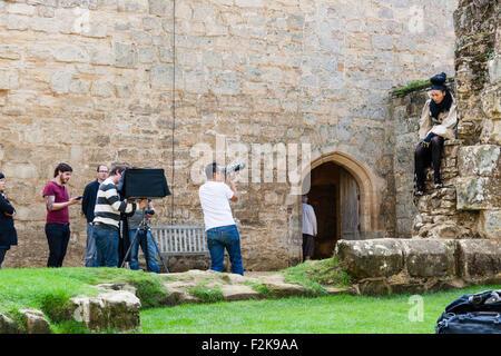 Modèle extérieur tirer. Dans le parc du château, modèle féminin asiatique est assis sur un mur en ruine tandis que Banque D'Images