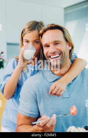 Portrait of happy father and daughter boire du lait et eating salad Banque D'Images