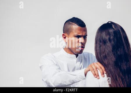 Portrait de jeune homme en colère face au café avec sa petite amie in front of white background Banque D'Images