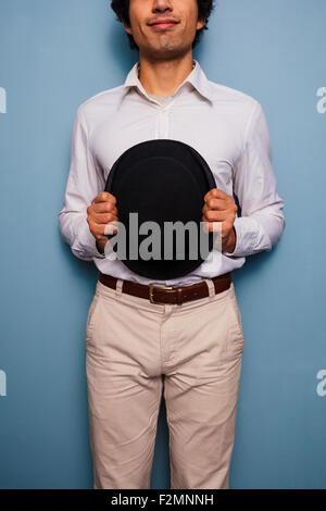 Jeune homme debout par un mur bleu avec un chapeau