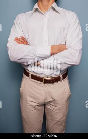 Jeune homme debout par un mur bleu avec les bras croisés Banque D'Images