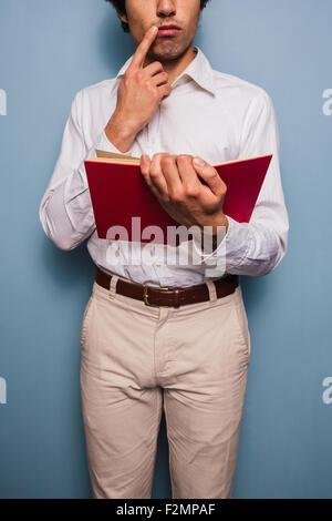 Jeune homme debout par un mur bleu reading book