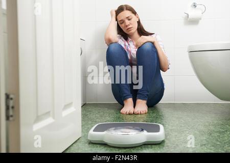 Malheureux Teenage girl looking at pèse-personne Banque D'Images