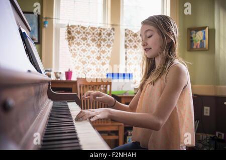 Caucasian girl playing piano dans la salle de séjour Banque D'Images