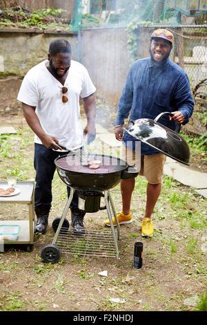 Les hommes noirs des hamburgers dans un barbecue cuisson Banque D'Images