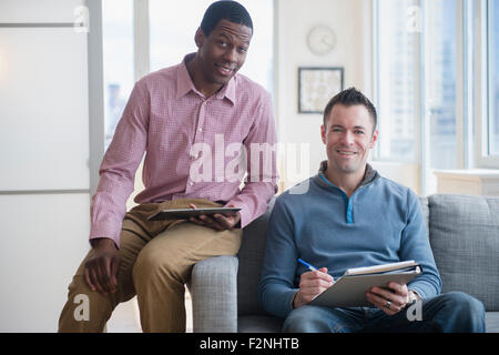 Hommes d'with digital tablet et bloc-notes sur canapé Banque D'Images