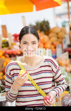 Hispanic woman eating fruit à farmers market Banque D'Images